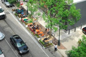 car parking spaces converted to outdoor eating area with trees, planter boxes, and people at tables and chairs