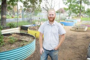 Peter standing near corrugated iron circular raised garden